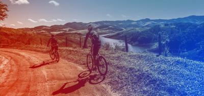 2 bicyclists riding on a country road